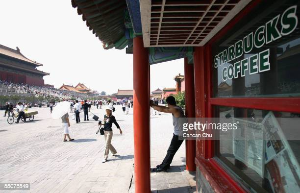 A visitor takes a break at Starbucks Coffee at the Forbidden City on September 6 2005 in Beijing China Starbucks opened its Forbidden City shop in...