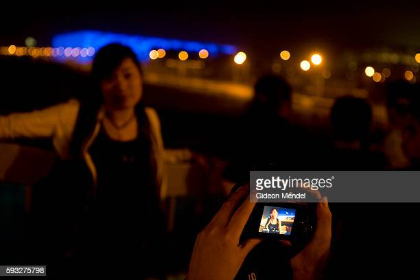 A visitor takes a digital photograph from a pedestrian bridge of the Olympic Park which is still under construction The National Aquatics Center is...