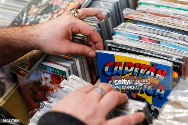 A visitor takes a look at an issue of Captain America comic book published by Marvel Comics during the 35th Comic Fair 2017 in Barcelona on March 30...