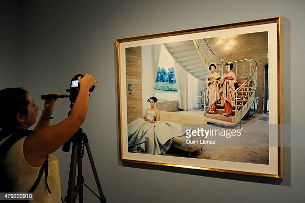 A visitor takes a photo at the photograph titled 'Carmen in Kyoto no 7' by Yelena Yemchuk during the opening for the press of 'Vogue like a painting'...