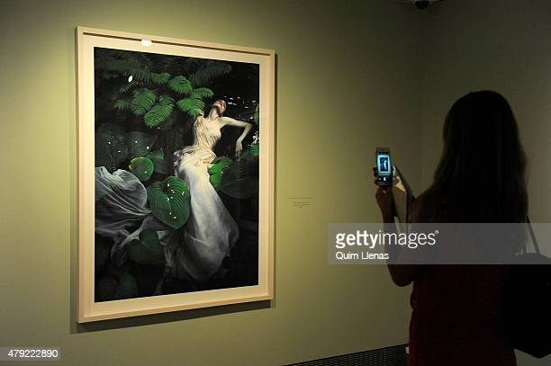 "Visitor takes a photo at the photograph titled ""Ofelia, Hever Castle, Kent"" by Mert Alas $ Marcus Piggott during the opening for the press of ""Vogue..."