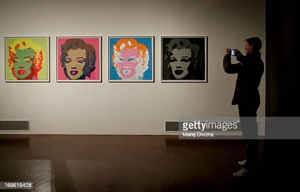 A visitor takes a photo of a collection by Andy Warhol during a press preview of the 'Marilyn' exhibition at Prague Castle on May 29 2013 in Prague...