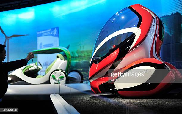 A visitor takes a photo of a futuristic electric car seat which changes angle according to the speed of the vehicle on display in the Shanghai...
