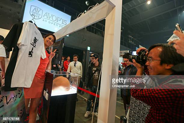 A visitor takes a photo of a Japanese adult model at a booth during the Japan Adult Expo at the Toyosu PIT on November 17 2015 in Tokyo Japan At the...