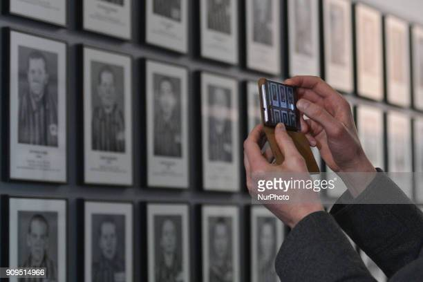 A visitor takes a photo of a permanent exhibition 'Evidence of crime' inside the Auschwitz 1 camp seen just a few days ahead of the 73rd anniversary...