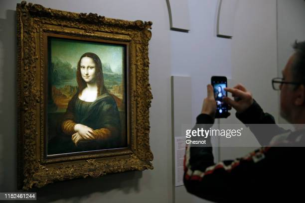 A visitor takes a photo of a portrait of Lisa Del Giocondo by the Italian artist Leonardo da Vinci a version of the Mona Lisa displayed during a...