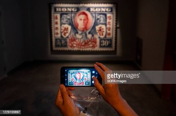 Visitor takes a photo of a poster of a British Hong Kong stamp featuring a portrait of King George VI at the Hong Kong museum of History. The...