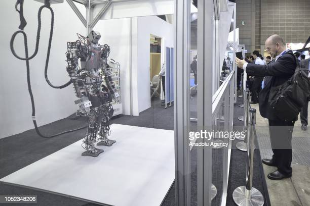 A visitor takes a photo of a robot displayed at the Japan Robot Week 2018 at Tokyo Big Sight on October 17 2018 in Tokyo Japan