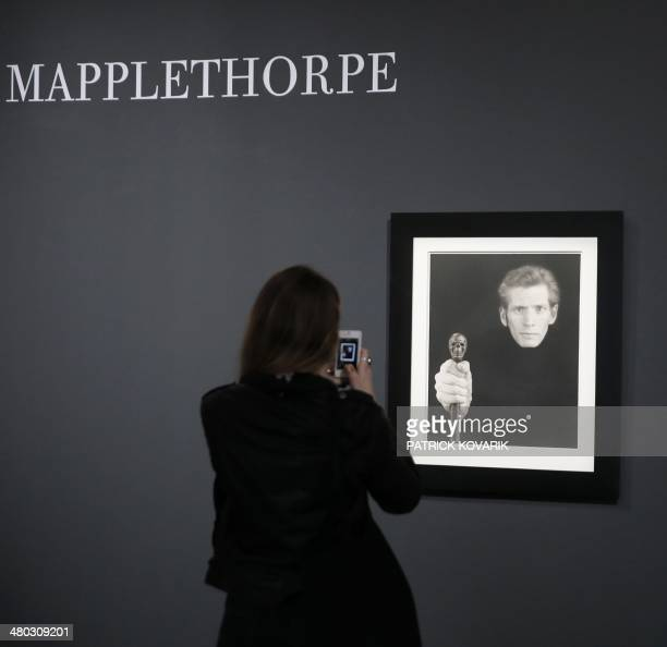 A visitor takes a photo of a selfportrait of the late US photographer Robert Mapplethorpe during the opening of an exhibition featuring his work at...