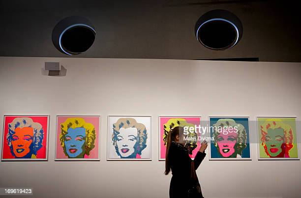 A visitor takes a photo of collection by Andy Warhol during a press preview of the 'Marilyn' exhibition at Prague Castle on May 29 2013 in Prague...