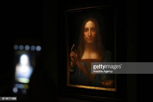 A visitor takes a photo of Leonardo da Vinci's Salvator Mundi painting at the Christie's in New York during its final day of viewing in New York...