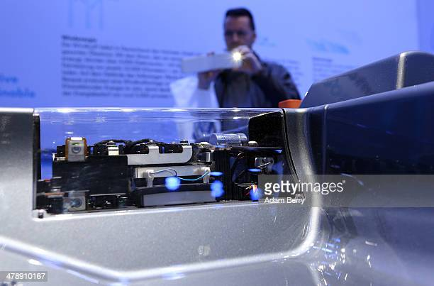 Visitor takes a photo of the battery of a Volkswagen e-Up! electric automobile at the Electric Mobility Week , a public Volkswagen event at the...