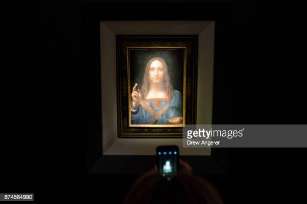 A visitor takes a photo of the painting 'Salvator Mundi' by Leonardo da Vinci at Christie's New York Auction House November 15 2017 in New York City...