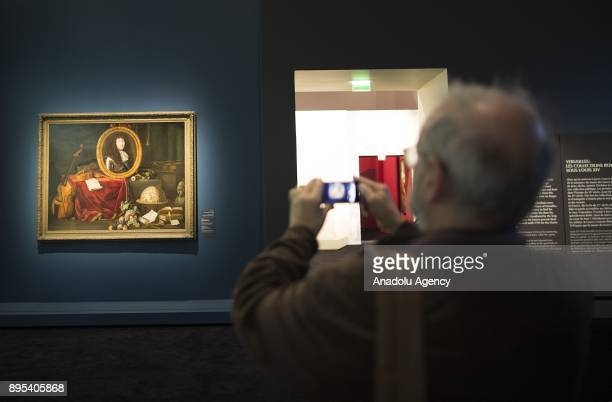A visitor takes a photo the art during the press preview of the 'From One Louvre to Another' exhibition at the Louvre Abu Dhabi in Abu Dhabi United...