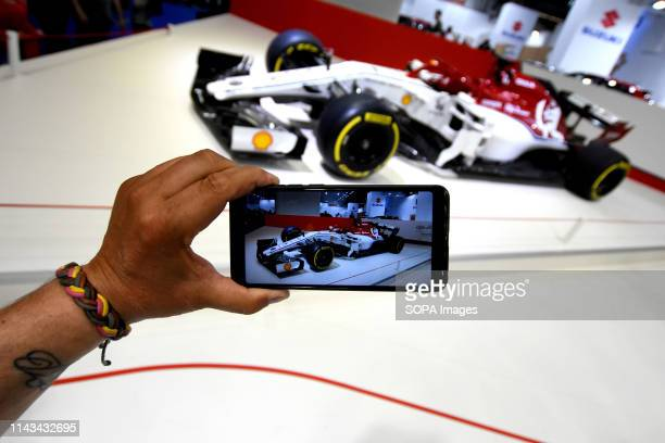 A visitor takes a photo with his smartphone of a Formula One Suzuki racing vehicle at the Automobile Trade Fair 2019 in Barcelona