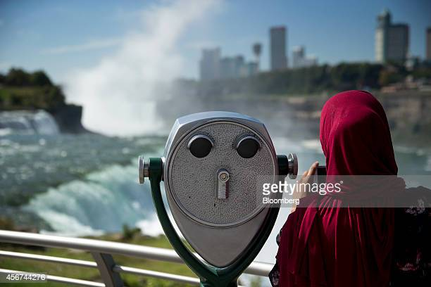 A visitor takes a photograph at Prospect Point next to a coin operated binocular at the American Falls in Niagara Falls New York US on Thursday Sept...