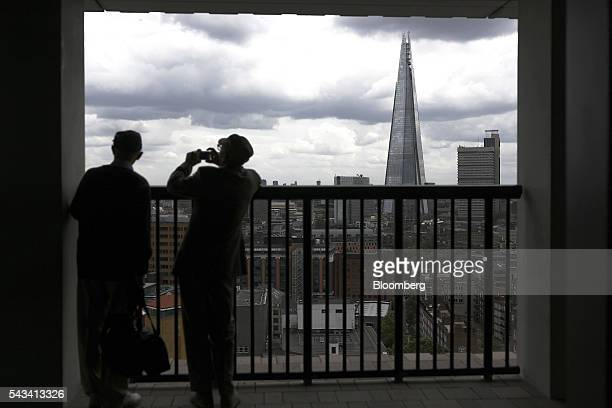 A visitor takes a photograph from the terrace of Switch House part of the Tate Modern art gallery as The Shard building stands beyond in London UK on...