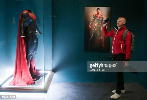 A visitor takes a photograph in front of a Superman costume used in the 'Man of Steel' 2013 movie during a press preview of 'DC Comics Exhibition...