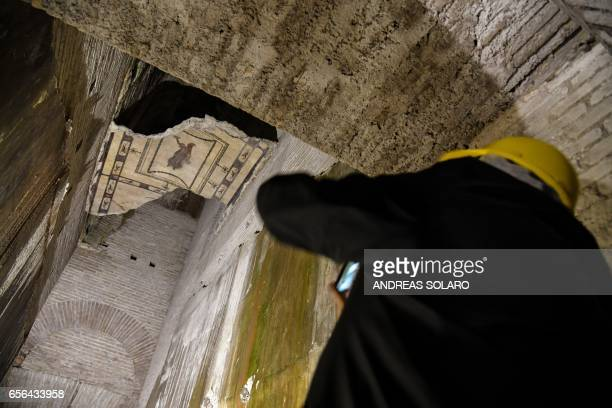 A visitor takes a photograph in one of the rooms of of the Domus Aurea a large palace built by the Roman Emperor Nero in the first century during a...