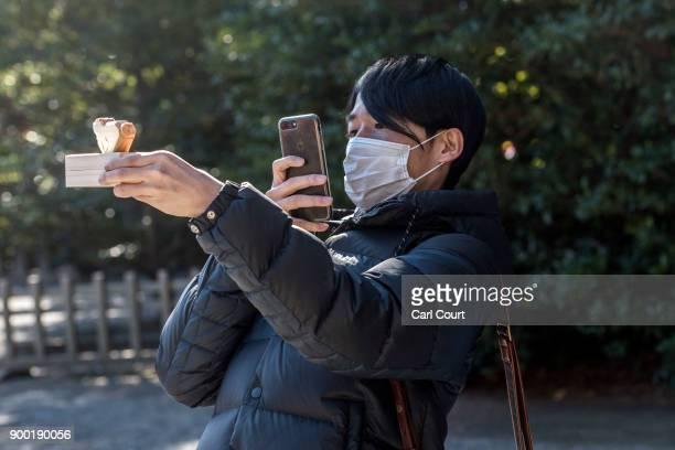 A visitor takes a photograph of a charm bought after new year prayers at Tsurugaoka Hachimangu Shinto shrine on January 1 2018 in Kamakura Japan...