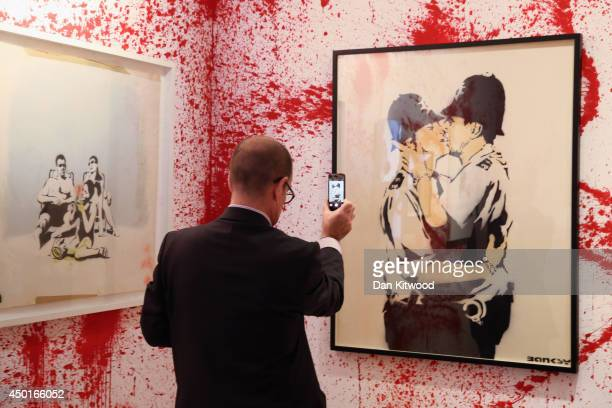 Visitor takes a photograph of a piece of work during a press preview of the first unauthorized retrospective of works by UK artist Banksy on June 6,...