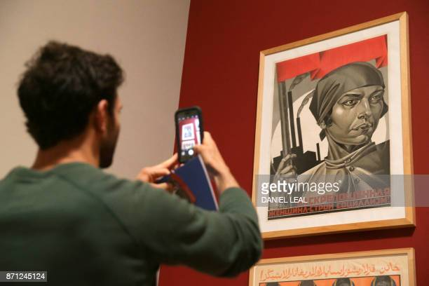 A visitor takes a photograph of artist Adolf Strakhov's Emancipated Woman Build Socialism c 1926 during the 'Red Star over Russia A revolution in...