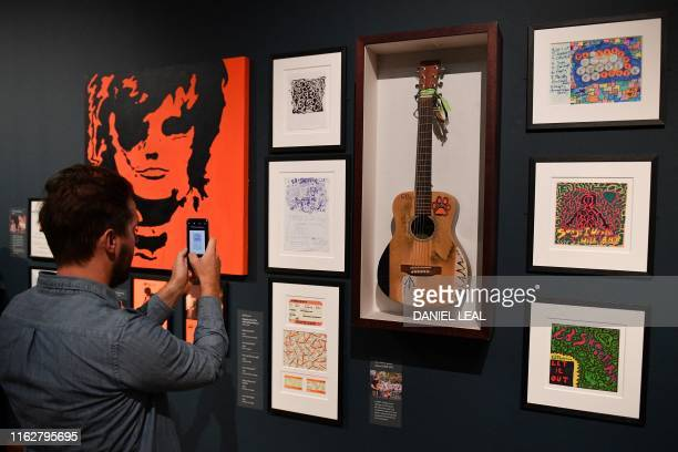 A visitor takes a photograph of British musician Ed Sheeran's 'Martin' guitar used by the artist between 20082012 during a press preview of the...