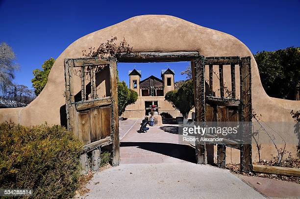 A visitor takes a photograph of her son in front of El Santuario de Chimayo in Chimayo New Mexico on February 27 2016 The Roman Catholic chapel built...