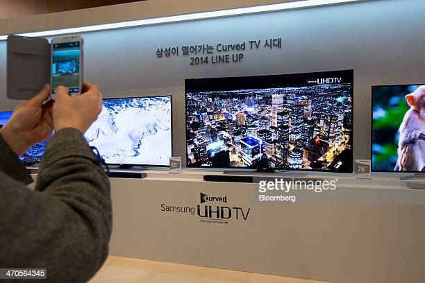 A visitor takes a photograph of Samsung Electronics Co curved Ultra High Definition televisions displayed at a media event using a Galaxy Note 2...