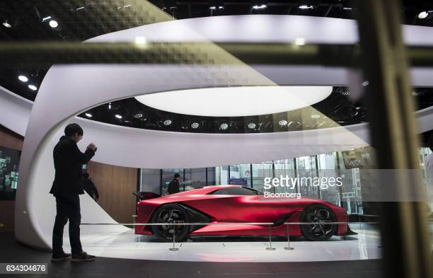 A visitor takes a photograph of the Nissan Motor Co Concept 2020 Vision Gran Turismo concept vehicle displayed at the company's Nissan Crossing...