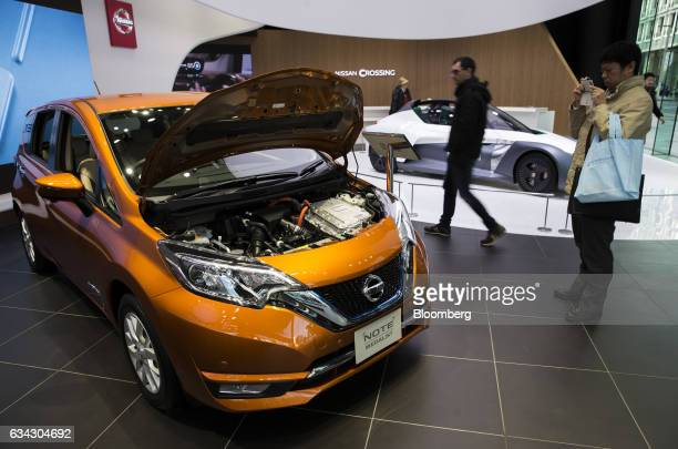 A visitor takes a photograph of the Nissan Motor Co Note ePower hybrid vehicle displayed at the company's Nissan Crossing showroom in the Ginza...