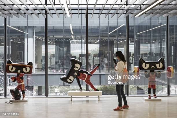 A visitor takes a photograph of TMall Cat statues in the gym at the Alibaba Group Holding Ltd headquarters in Hangzhou China on Friday Sept 8 2017...