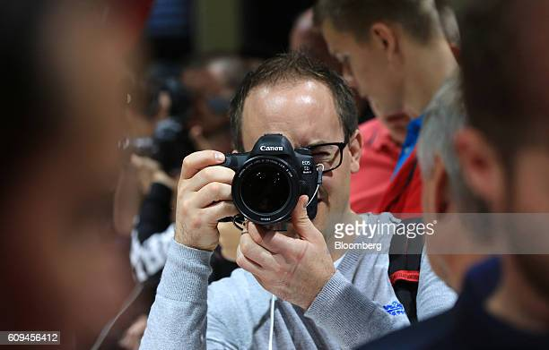 A visitor takes a photograph using a Canon EOS 5D MK IV digital camera manufactured by Canon Inc during the Photokina photography trade fair in...