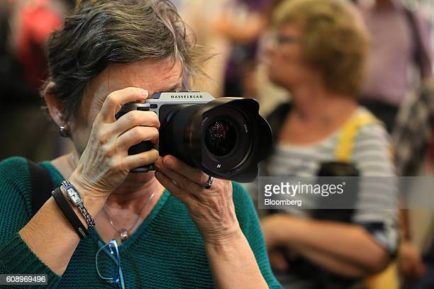 A visitor takes a photograph using the Hasselblad X1D a mirrorless medium format digital camera manufactured by Hasselblad A/S during the Photokina...