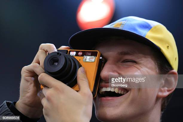 A visitor takes a photograph using the Leica Sofort the first instant camera manufactured by Leica Camera AG during the Photokina photography trade...
