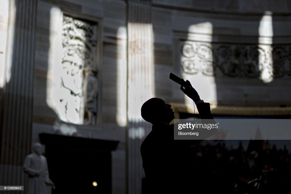 A visitor takes a photograph with a mobile device in the Rotunda of the U.S. Capitol in Washington, D.C., U.S., on Tuesday, Jan. 30, 2018. President Donald Trump plans to promote the Republican tax overhaul he signed into law in his first State of the Union speech on Tuesday night, but fiscal headwinds mean hes likely to have less legislative success in his second year in office. Photographer: Andrew Harrer/Bloomberg via Getty Images
