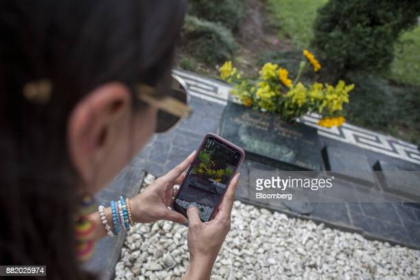 A visitor takes a photograph with a mobile device of the grave site of narcotics kingpinPablo Escobar at the Montesacro Cemetery in Medellin...