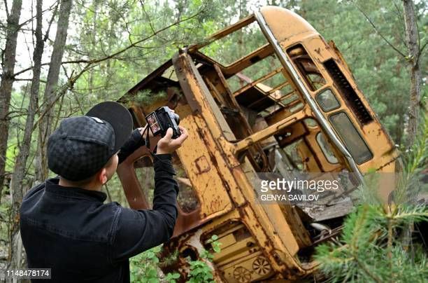 A visitor takes a picture at a wreckage of a bus in the ghost city of Pripyat during a tour in the Chernobyl exclusion zone on June 7 2019 HBOs...