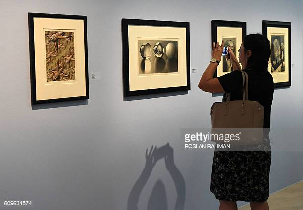 A visitor takes a picture at the art exhibition 'Journey to Infinity Escher's World of Wonder' which showcases the works of world famous graphic...