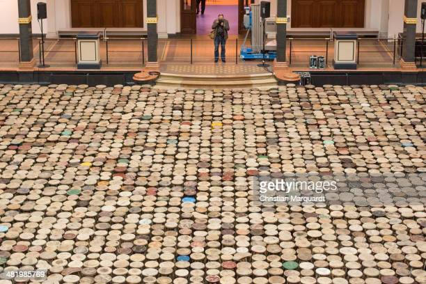 A visitor takes a picture from the work 'Stools' at the press preview for Chinese artist Ai Weiwei 'Evidence' exhibition at Martin Gropius Bau on...