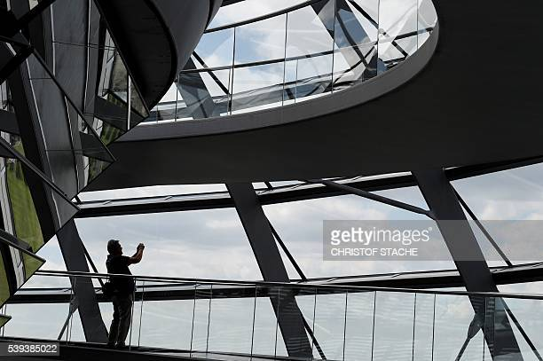 Visitor takes a picture in the glass cupola of the Reichstag building that hosts the German parliament in Berlin, Germany, on June 10, 2016. / AFP /...