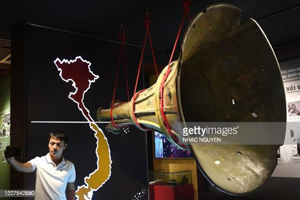 Visitor takes a picture next to a loudspeaker replica used for transmitting propaganda messages from the North to the South Vietnam during the...