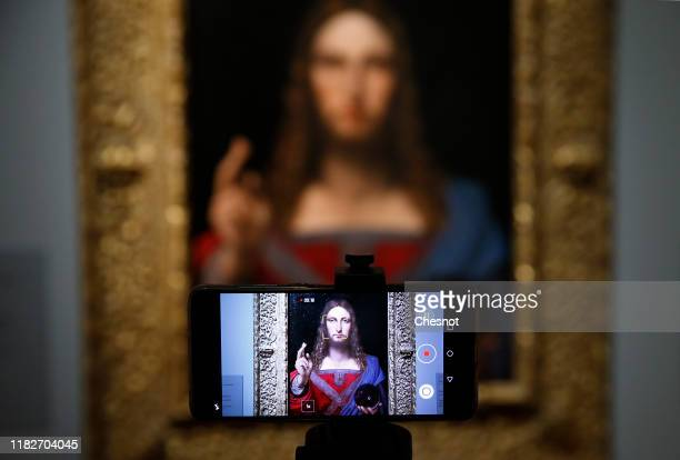 A visitor takes a picture of a painting entitled 'Salvator Mundi' by School of Leonardo da Vinci during a press visit of the exhibition Leonardo da...