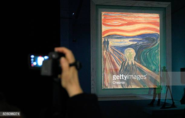 """Visitor takes a picture of a painting The scream of Edvard Munch as part of the opening of the exhibition """"Keys to a Passion"""" at the Louis Vuitton..."""