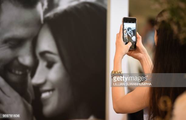 A visitor takes a picture of a photo display during the launch of an exhibition commemorating the royal wedding of Britain's Prince Harry and US...