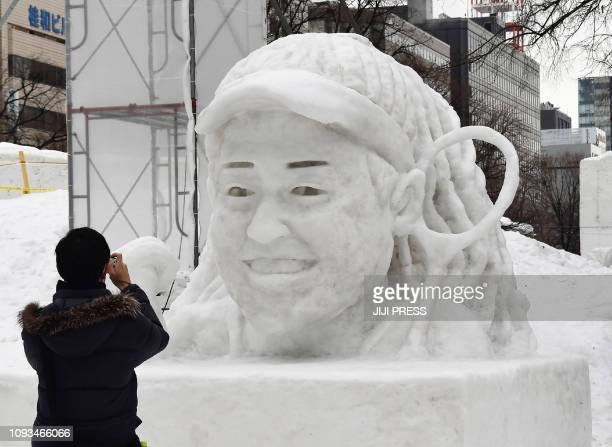 A visitor takes a picture of a snow statue featuring tennis player Naomi Osaka during the opening day of eightday Sapporo Snow Festival in Sapporo on...