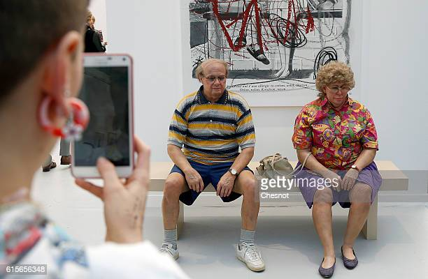 A visitor takes a picture of an artwork entitled 'Old Couple on a Bench' by US artist Duane Hanson at the Grand Palais as part of the FIAC...