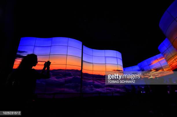 A visitor takes a picture of an OLED television installation at the booth of LG during a preview day of the IFA the world's leading trade show for...