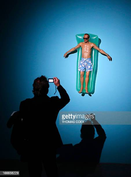 A visitor takes a picture of 'Drift' a sculpture by Australian artist Ron Mueck exhibited at the Fondation Cartier pour l'art contemporain on April...