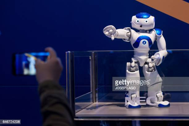 A visitor takes a picture of NEC's NAO robot during the Mobile World Congress on the third day of the MWC in Barcelona on March 1 2017 Phone makers...